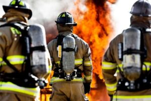 A photo of firefighters looking away from the camera at an out of control fire, wearing firefighting PPE.