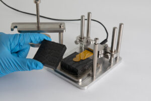 An image depicting testing of a polymer composite in a TPS test clamp. The sensor is mounted on a clamp which is attached to a frame. The active part of the sensor - a thin yellow film - rests on top of a black polymer piece on top of a test platform. A gloved hand is visible on the left in the process of loading the upper sample specimen on top of the sensor in advance of clamping the pieces together for testing.